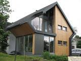 Modernistično zasnovana družinska hiša s kombinacijo klasične in macesnove fasade.